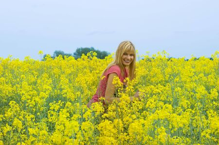 happy blond girl enjoying in a yellow field and smiling Stock Photo - 4941542