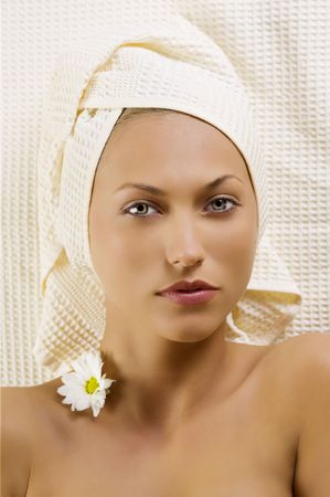 nice portrait of young and pretty woman with bath towel and flowers on neck  photo