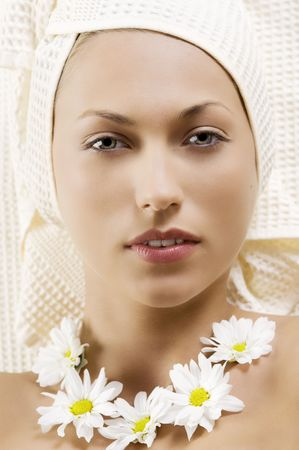 nice portrait of a young woman with bath towel and flowers on neck photo