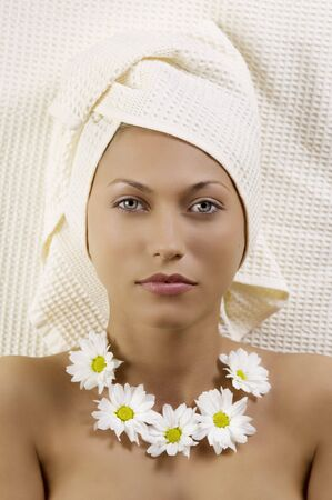 pretty young woman with bath towel and flowers as necklace laying down photo