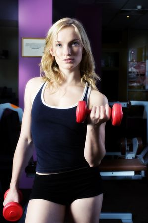 blond cute woman doing exercise with dumbbells in front of mirror forced color photo