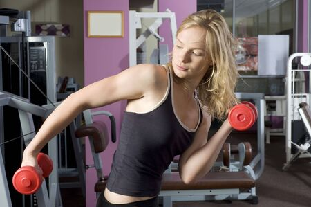 blond cute woman doing exercise with red dumbbells in fitness club photo