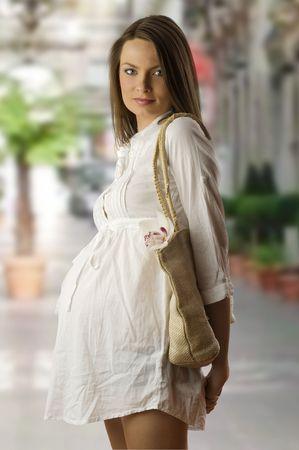 life giving birth: muy bonita mujer embarazada prenatal en blanco vestido con saco para ir de compras Foto de archivo