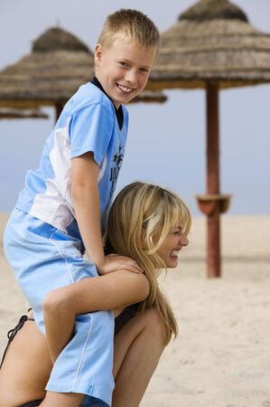 young blond woman carrying on the shoulder her little brother