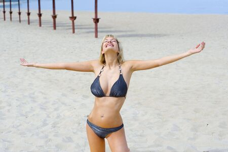 cute blond woman in bikini on thye beach smiling to the sun photo