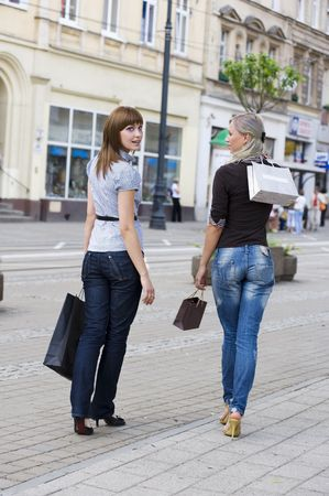 two young beautiful women walking on the street shop carrying shopping begs  photo