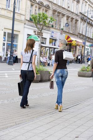 two young beautiful women walking on the street shops with shopping bags photo