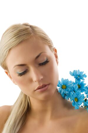 pretty blond girl in a beauty portrait with blue daisy on her shoulder