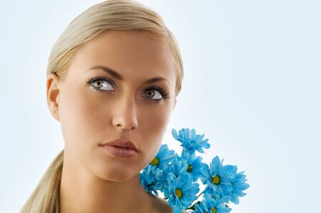 pretty blond girl in a beauty portrait with blue daisy on her shoulder Stock Photo - 5204927
