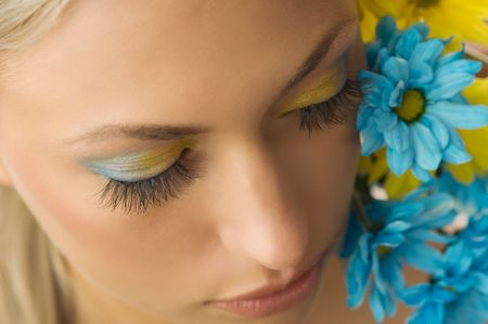 nice beauty portrait of pretty blond girl with blue and yellow daisy and colored makeup Stock Photo - 5288600