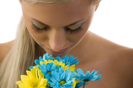 cute blond woman with colored make up in act to smell some daisy Stock Photo - 5288597