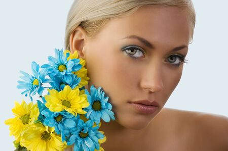 beauty portrait of pretty young blond girl with blue and yellow daisy near her face Stock Photo - 5288599