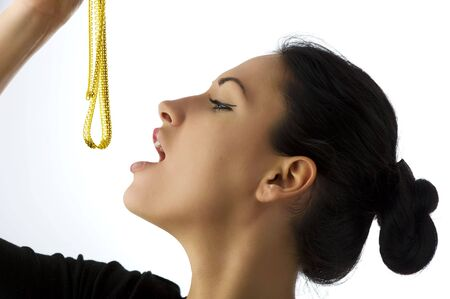 portrait of a cute woman in act to eat a golden necklace Stock Photo - 5299492