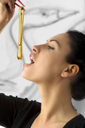 portrait of a cute woman in act to eat gold neck kept with chopstick Stock Photo - 5299498