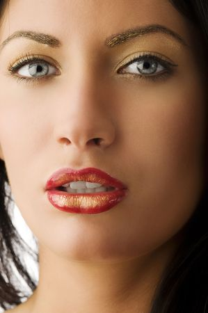 glitter gloss: beauty shot of beautiful and young woman with golden creative make up