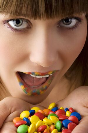 close up of young girl with open colored mouth and a lot of multicolor smarties near photo