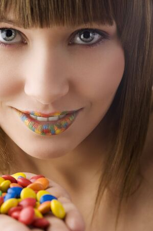 nice portrait of young pretty girl with colored smarties in hand a multi color lips photo