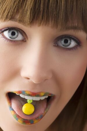 close up of young girl with multicolor lips and a yellow candy on her tongue photo