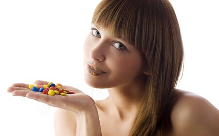 nice portrait of cute model looking in camera with some smarties and multicolor lips photo