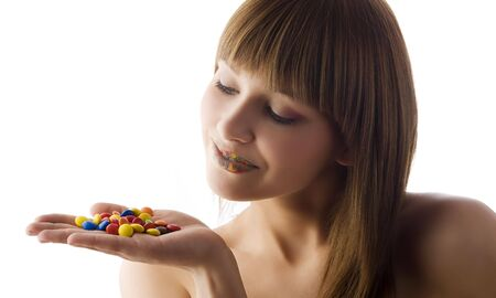 cute girl with multicolor lips in white background loonking some colored candy photo