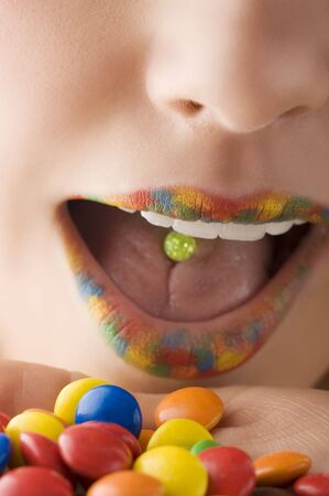 close up of a mouth with multicolor lips and colored smarties  photo