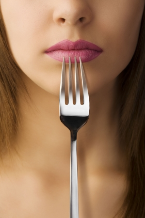 close up of woman mouth with pink lipstick keeping a fork near the lips photo
