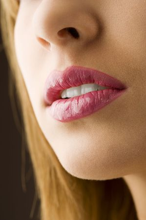 wet lips: close up on a woman mouth pink colored and wet lips