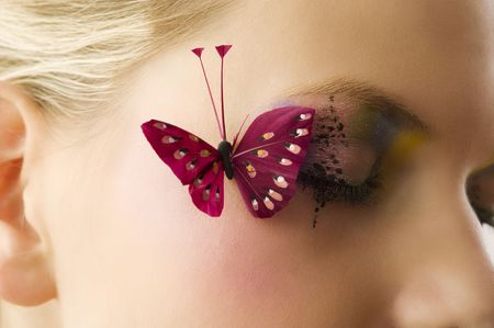 artificial model: woman eyes close up with creative makeup and a red butterfly