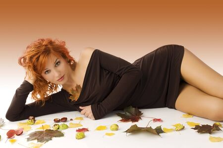 amazing red haired woman laying down on white floor with autumn leaves and chestnut all around photo