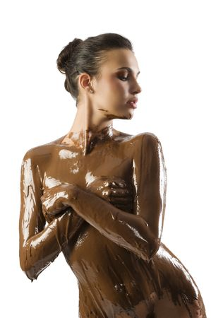amazing shot of a young beautiful brunette with her naked body covered of sweet cream chocolate Banque d'images