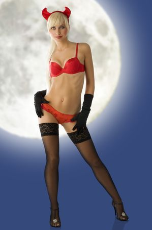 sexy blond with devil horns in red lingerie and black gloves looking in camera