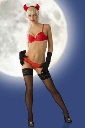 sexy blonde met de duivel hoorns in rode lingerie en zwarte handschoenen kijken in de camera Stockfoto