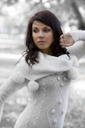 outdoor portrait of a young pretty brunette wearing a white warm sweater photo