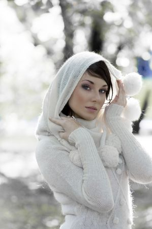fashion portrait of a young pretty brunette wearing a white warm sweater with hood in winter forest  photo