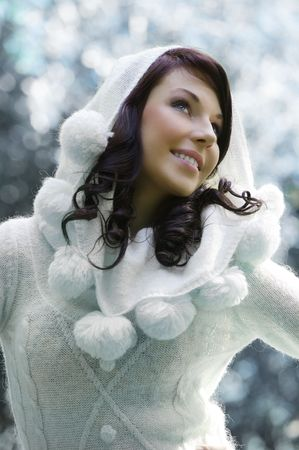 pretty young woman with a white sweater with hood in a outdoor winter portrait