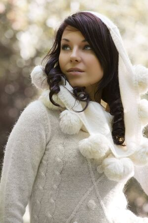 outdoor portrait of a young pretty brunette wearing a white warm sweater with hood photo