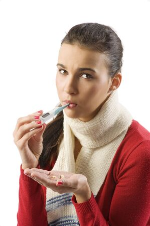 portrait of young brunette with red sweater and white scarf checking her body temperature photo