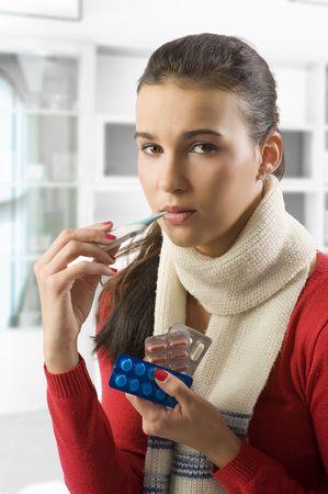 Closeup portrait of cute brunette woman checking her body temperature photo