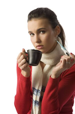 nice brunette with a thermometer fighting against a cold with a cup of hot drink photo