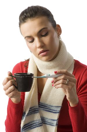 woman with a cup of hot drink looking sick checking her body temperature photo
