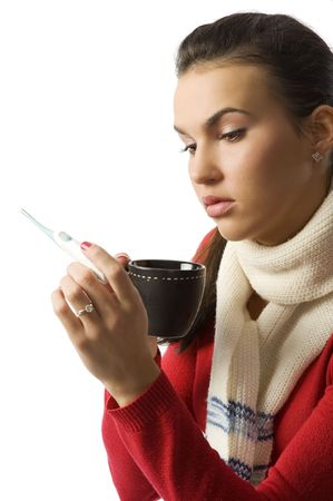 Closeup portrait of young ill woman checking her body temperature and drinking a cup of tea  photo