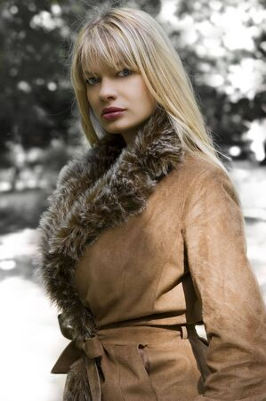 beautiful blond girl with winter jacket with fur in a park in a sunny winter day photo