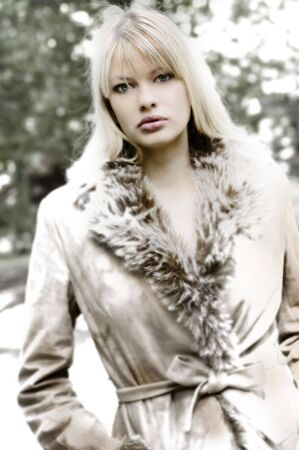 fur tree: beautiful blond in winter dress with snow in a fahion shot looking iced