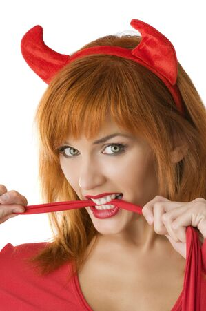 close up of a red haired girl with horns like a devil biting a red tail  photo