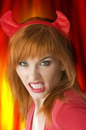 portrait of woman with halloween horns grinding her teeth like a vampire  photo