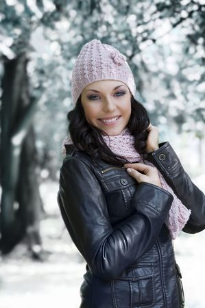 nice girl in winter dress with leather jacket and pink scarf and hat in a park with snow photo