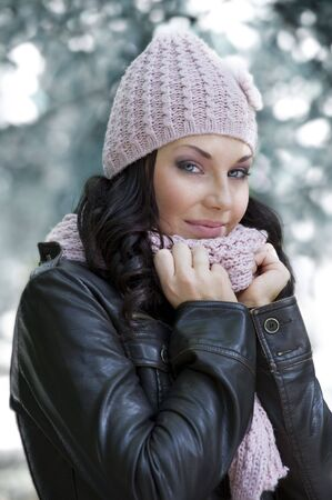 nice girl in winter dress with leather jacket and pink scarf and hat in a park Stock Photo - 5669746