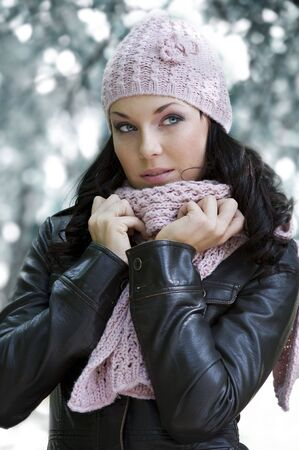 nice girl in winter day outside in park dressing leather jacket and pink scarf and hat photo