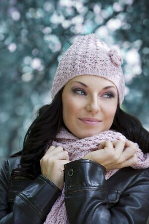 outdoor portrait of a young pretty brunette with pink scarf and hat in a winter day photo
