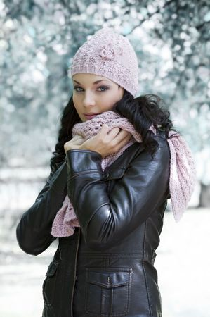 actress: pretty woman in black jacket and pink scarf a winter day outside in park Stock Photo